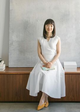 Japanese organizing + decluttering guru Marie Kondo, wearing a white linen dress and seated on a built-in contemporary bench in a minimalist room with gray wall behind her.